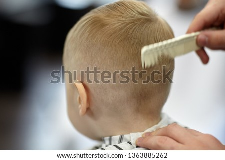 Cute blond baby boy in a barber shop having haircut by hairdresser. Hands of stylist with hairbrush. Children's fashion. Indoors, back view, copy space.