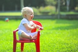 Cute blond baby girl laughing and enjoying the sun sitting on a small red chair in a garden