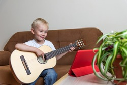 Cute blond boy plays the guitar and looks at the tablet standing on the table. A fun online lesson on the internet. Digital education in self isolation mode. Modern lifestyle. Stay at home.