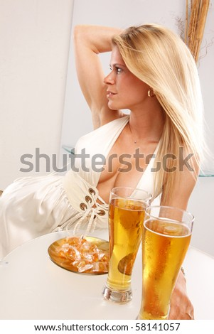 Cute blond enjoys a cold beer at a table