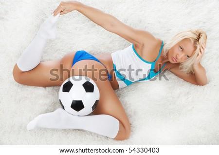 Cute blond fan lying with ball
