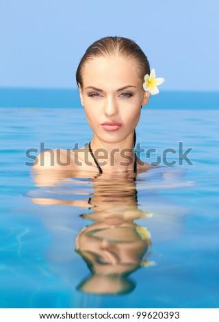 Cute blond girl relaxing in swimming pool