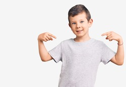 Cute blond kid wearing casual clothes looking confident with smile on face, pointing oneself with fingers proud and happy.