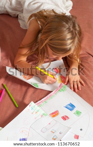 Cute blond little girl drawing on the paper.