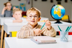 Cute blond male student in eyeglasses in class with globe in elementary school. Portrait of little schoolboy studying with classmates in background.