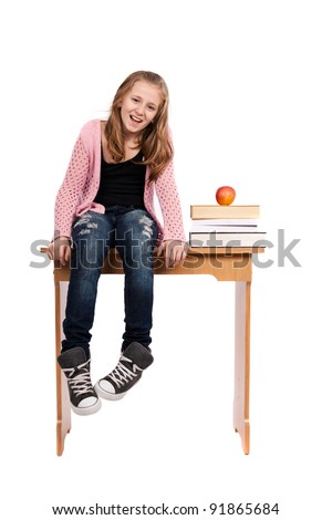 Cute blond schoolgirl sitting on her desk with a pile of books nearby
