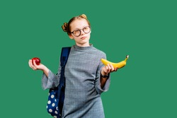 Cute blond thoughtful girl wearing two buns with blue backpack polka dot holdig apple and banana over green chalk board on background. Back to school, study concept.