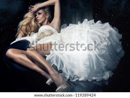 Cute blond woman in gorgeous dress in the stars