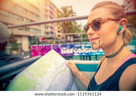 Cute blond woman riding on the bus with headphones in ears and with map in hands, discovering points of interest of Barcelona, active summer vacation in Europe
