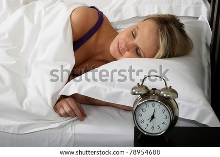 Cute blond woman waking up in bed with alarm clock