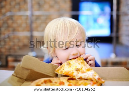 Cute blonde boy eating slice of pizza at fast food restaurant. Child unhealthy meal concept. Hungry kid. Pizza recipe.