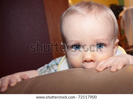 Cute blonde boy with blue eyes chews on furniture while looking into camera