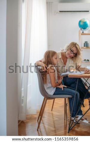 Cute blonde Caucasian schoolgirl doing homework with her mother helping.