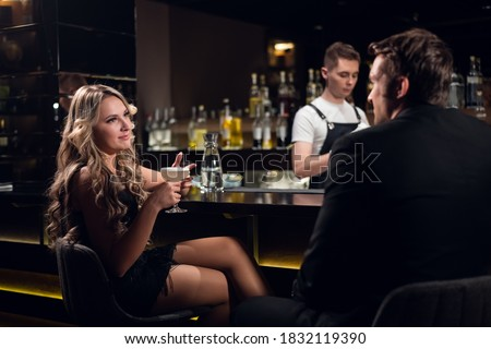 cute blonde flirts with a man in a jacket in a nightclub. Stock photo ©