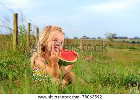 Cute blonde girl eats a watermelon in a field