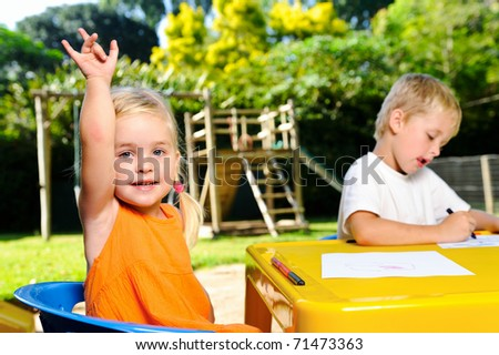 cute blonde girl holds hand up for attention at kindergarten