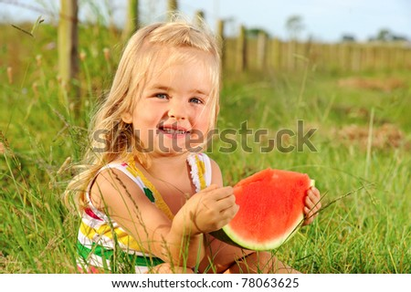 Cute blonde girl is going to eat a slice of watermelon while sitting in the grass