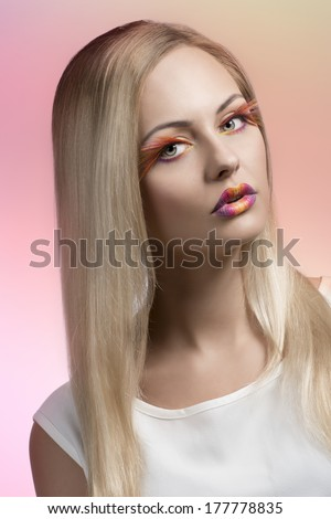 cute blonde girl with creative colorful make-up and feathered eyelashes, long silky smooth hair and white dress