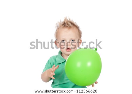 Cute blonde hair blue eyed baby boy wearing green top and holding green balloon on his birthday celebration