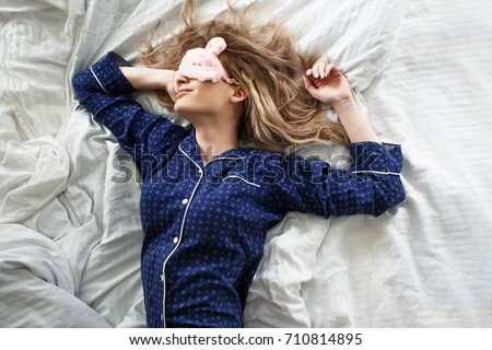 Cute blonde in her bed in blue pajamas and sleep mask, top view