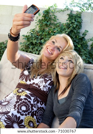 Cute blonde mother and teenage daughter taking their picture with a mobile cell phone camera.