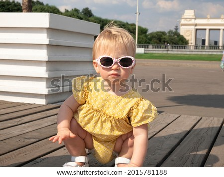 Cute blonde stylish baby girl with sunglasses wearing beautiful yellow dress sitting on hunkers in city park, looking at camera.Kid fashion, child care or spending time outdoors in summer concept. Stockfoto ©