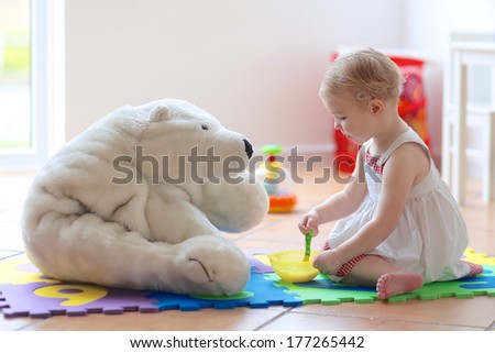 Cute blonde toddler girl feeding her white teddy bear with porridge from spoon sitting indoors at home or kindergarten in a bright room with big window