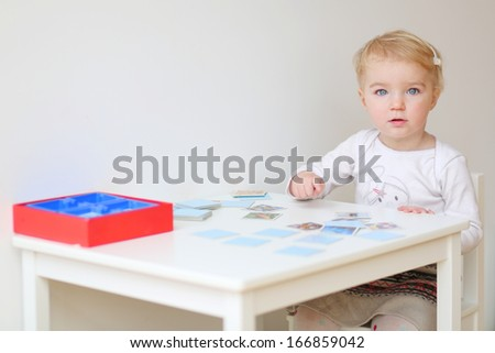 Cute blonde toddler girl playing memory game sitting at little white table indoors at home or kindergarten