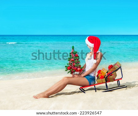 Cute blonde woman at sea beach in santa hat sitting at sled with christmas tree and gift boxes - Happy New Years concept