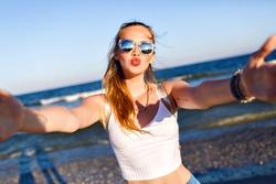 Cute blonde woman making selfie near ocean, having fun and sending air kiss , travel alone, tropical luxury beach vacation, sunglasses, backpack, pretty face.