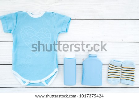 Cute blue baby clothes for boy. Bodysuit, socks, cosmetics on white wooden background top view copy space