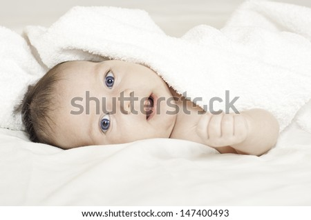 Cute blue-eyed newborn baby. Can be used in journal or packaging or as postcard concept.