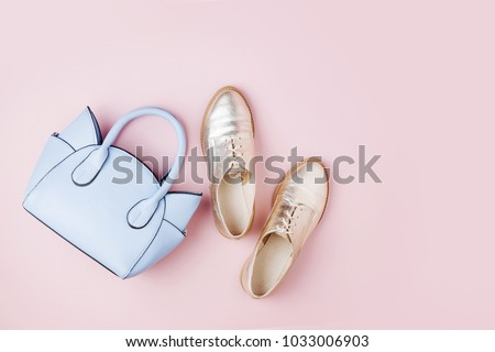 Cute blue ladies bag and stylish golden shoes. Flat lay, top view. Spring fashion concept in pastel colored