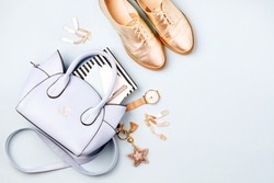 Cute blue ladies bag, stylish golden shoes and  feminine accessories . Flat lay, top view. Spring fashion concept in pastel colored