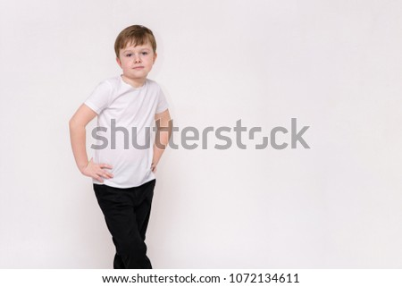 cute boy aged 6 years shows on a white background in different poses different emotions