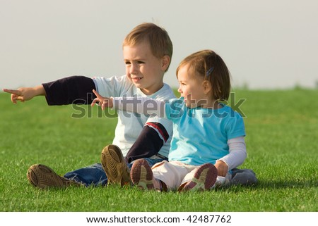 Cute boy and baby sister sat on grass pointing in same direction.