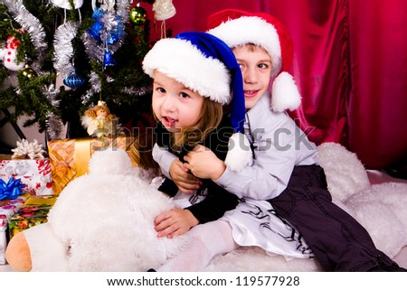 Cute boy and girl in Santa's hats with presents