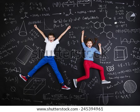 Cute boy and girl learning playfully in frot of a big blackboard Foto stock ©
