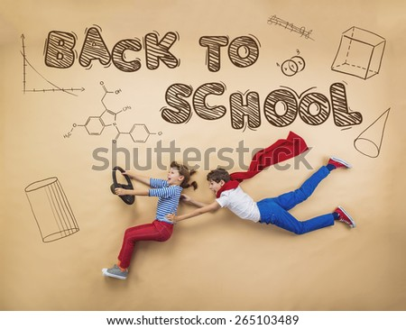 Cute boy and girl learning playfully in frot of a big blackboard. Studio shot on beige background. Foto stock ©