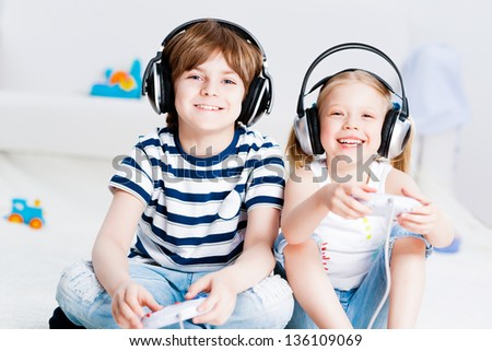 cute boy and girl playing gaming console in wireless headphones, sitting on the floor
