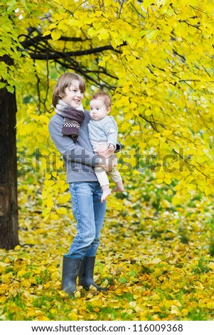 Cute boy and his baby sister standing under a colorful autumn tree