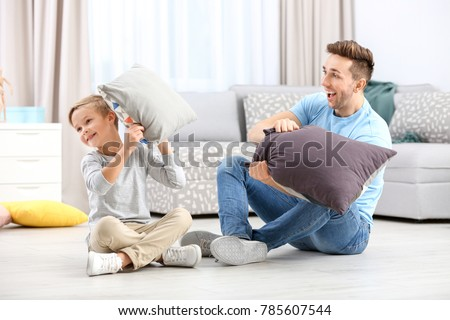 Cute boy and his father fighting pillows at home
