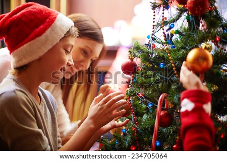 Cute boy and his mother decorating Christmas tree for holiday #234705064