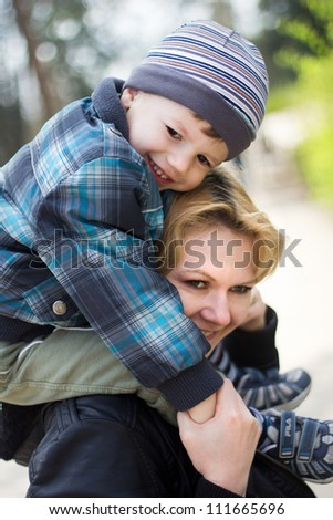Cute boy and mother smiling at park