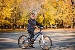 Cute boy cycling in autumn park