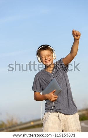 Cute boy dancing to the rhythm with headphones and digital tablet outdoors.