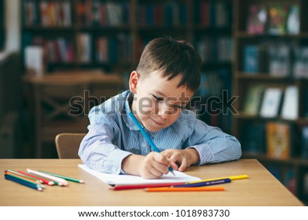 Cute  boy doing homework,  coloring pages, writing and painting. Children paint. Kids draw. Preschooler with books at home. Preschoolers learn to write and read. Creative boy. #1018983730