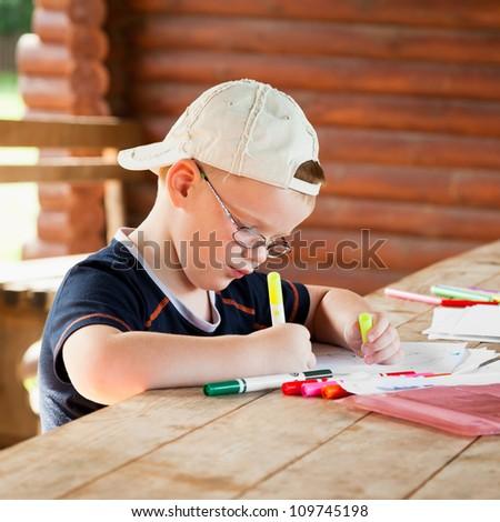 cute boy drawing in wooden gazebo outdoors
