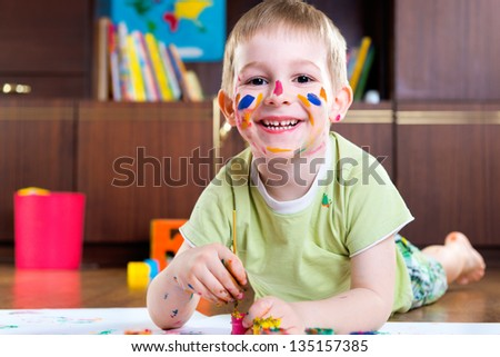 Cute boy drawing with colorful paints