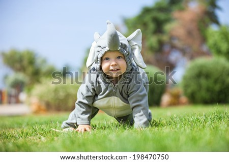 Cute boy dressed in elephant costume crawling on the lawn